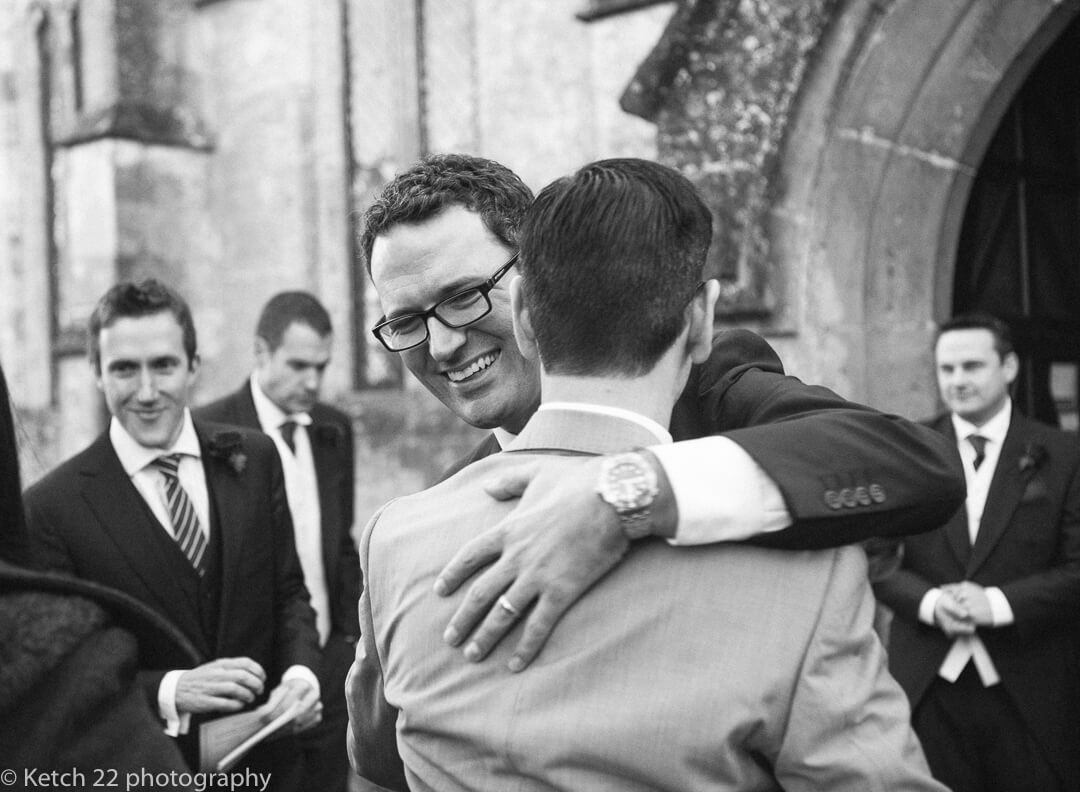 Best man greeting wedding guest outside Church in Gloucestershire