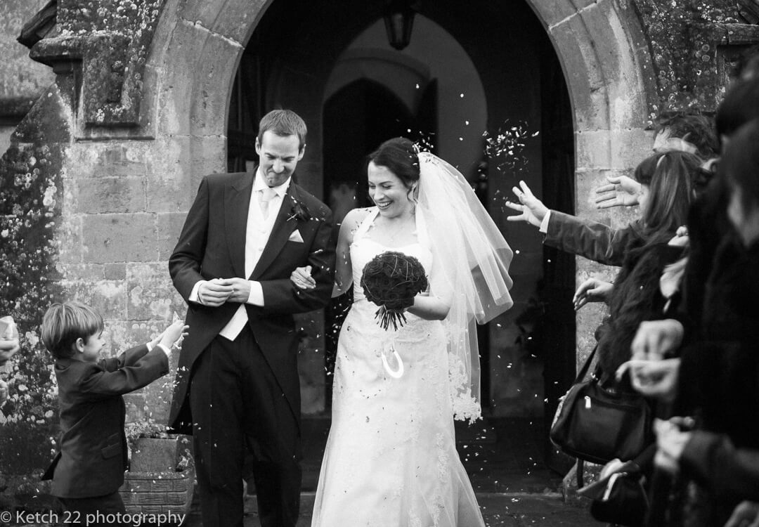 Bride and groom getting covered in confetti at documentary wedding in Gloucestershire