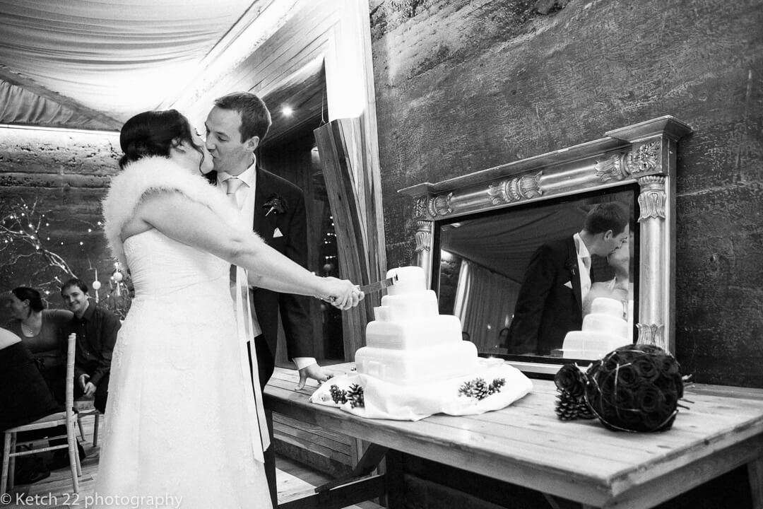 Bride and groom kissing whilst cutting the wedding cake