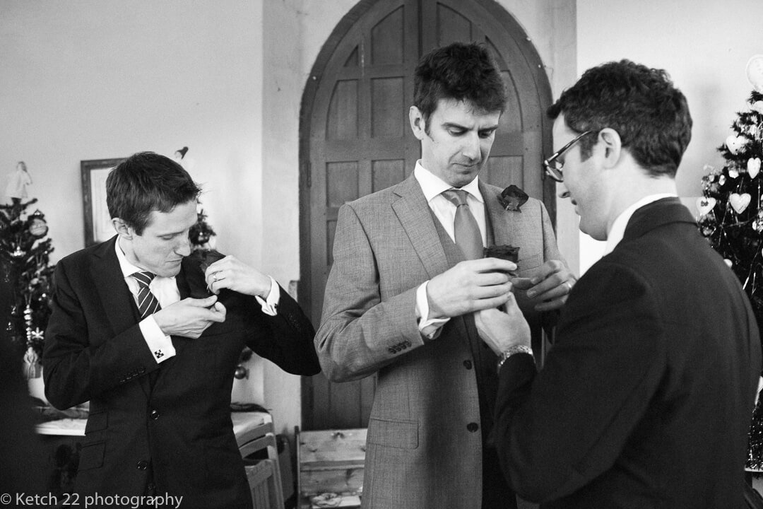 Grooms men pinning their flowers on jacket at reportage wedding
