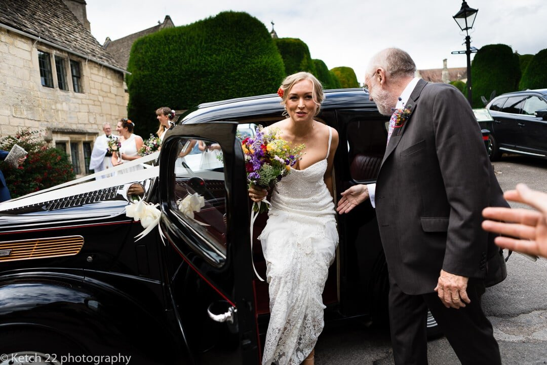 Bride getting out of wedding car in Painswick