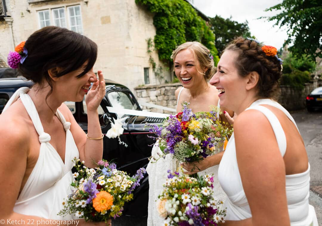 Bride and bridesmaids giggling just before wedding ceremony