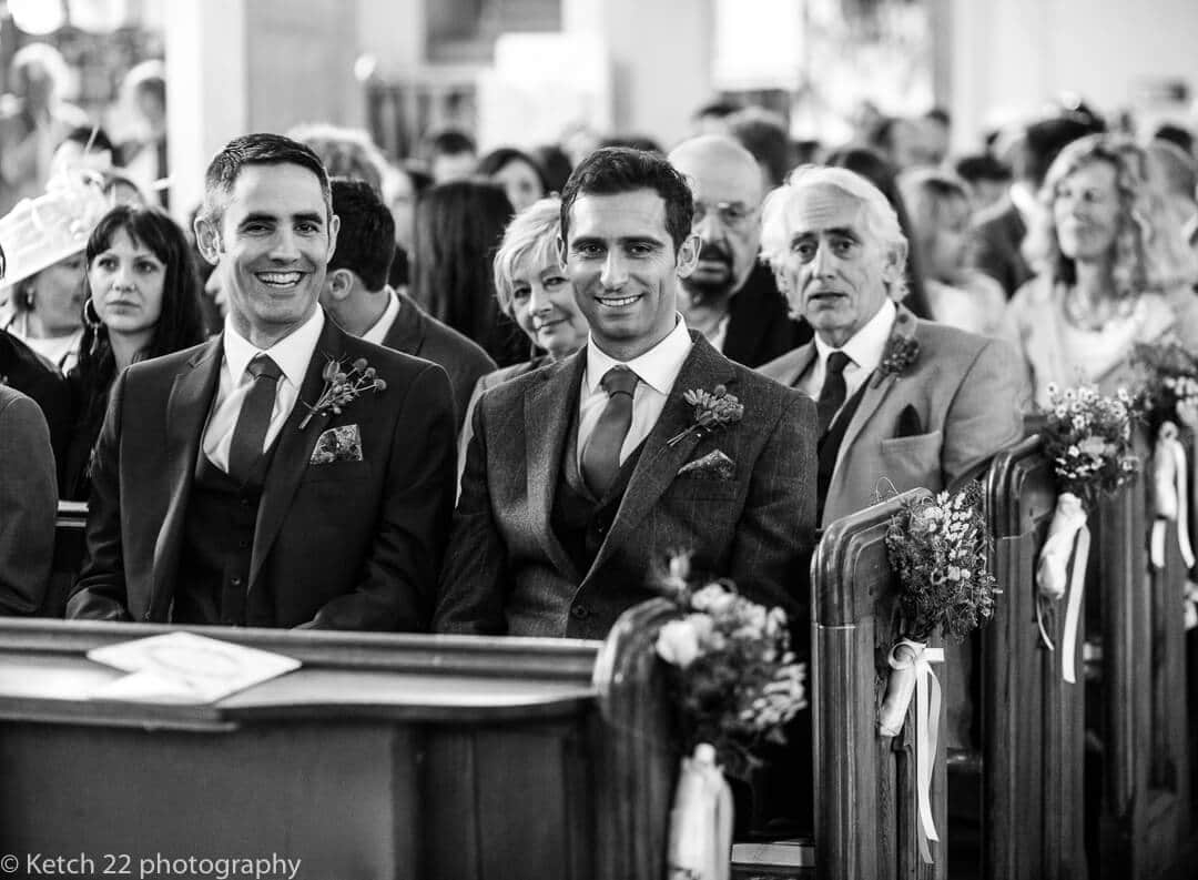 Groom and best man looking relaxed in church just prior to the wedding ceremony