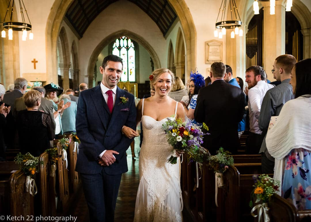 Bride and groom leaving painswick church after wedding ceremony