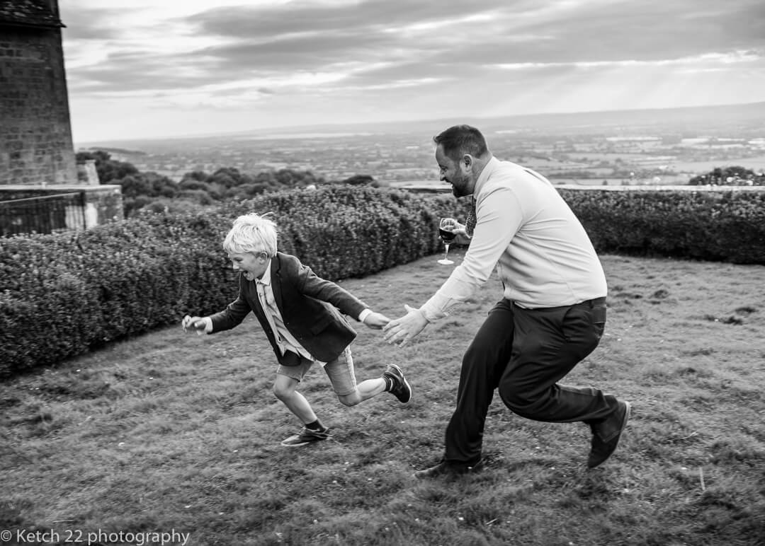 Father chasing his son at wedding