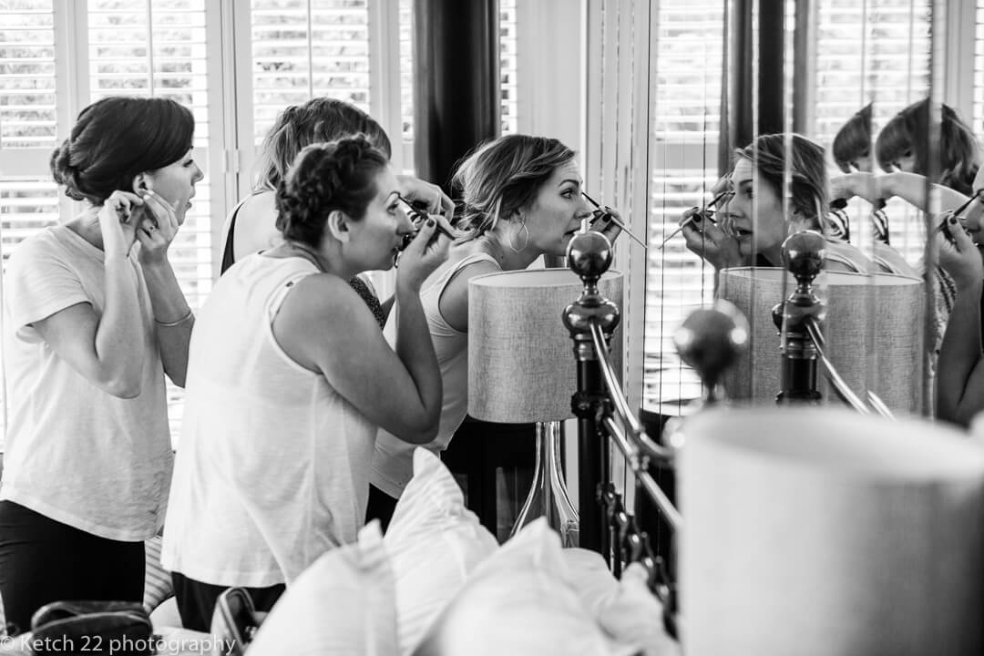 Bridesmaids putting on make up at bridal preparations
