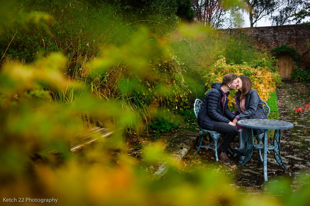 Engaged couple kissing in garden in the autumn