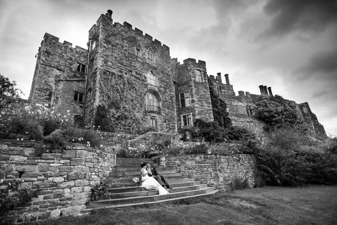 Bride and groom sat on steps in front of Berkeley Castle wedding venue