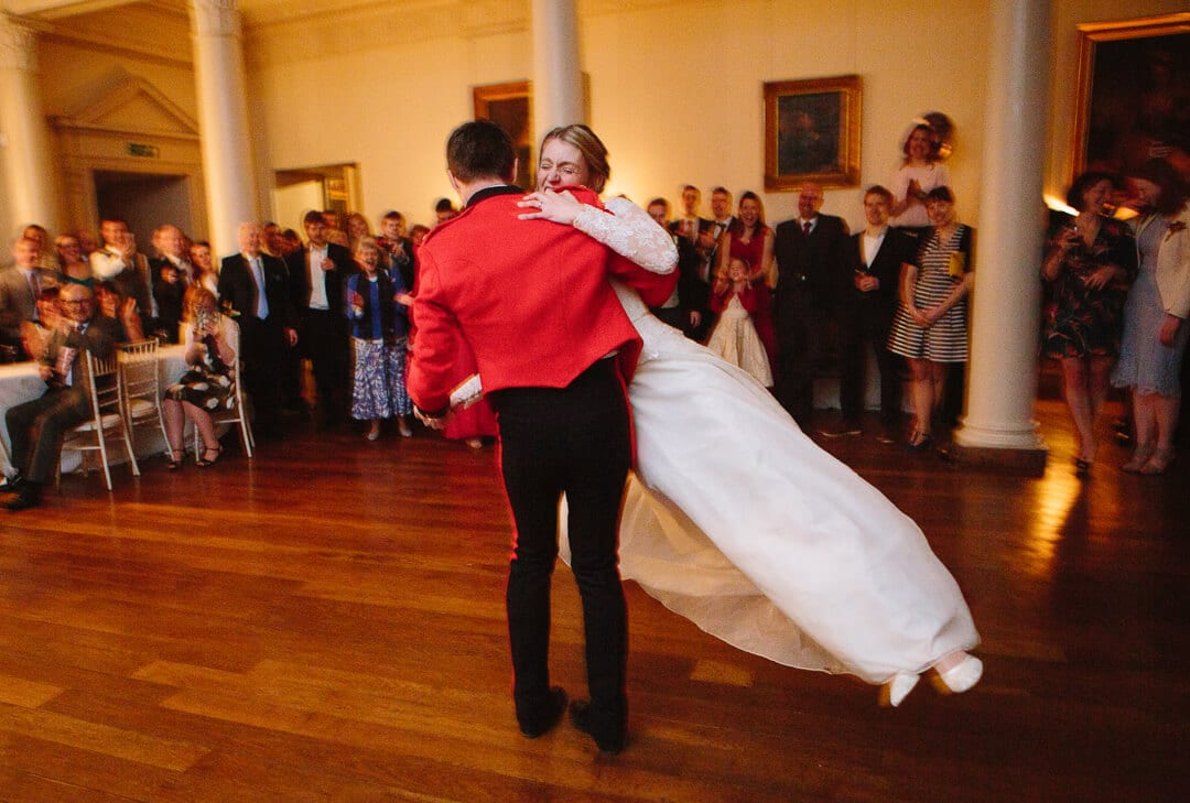 Groom in red army jacket spinning bride at first dance