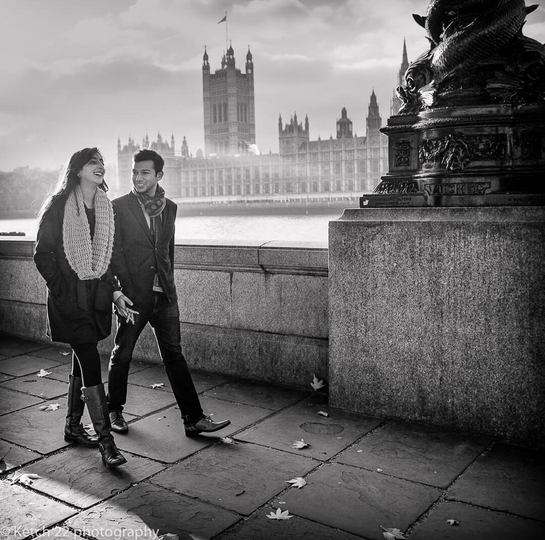 Engaged couple walking and chatting by the river Thames at The Houses of Parliament in London