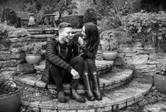 Engaged couple laughing on steps in garden