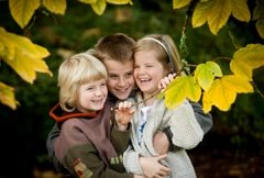 Portrait of kids laughing with autumn leaves
