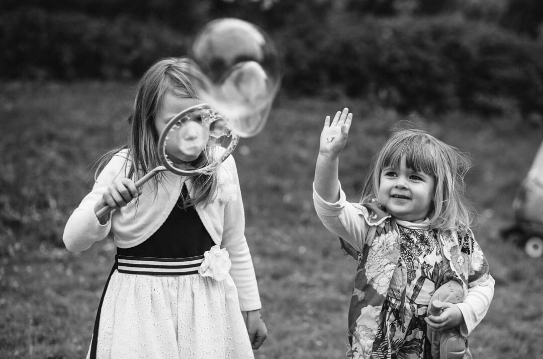 Kids playing with bubbles at rural wedding
