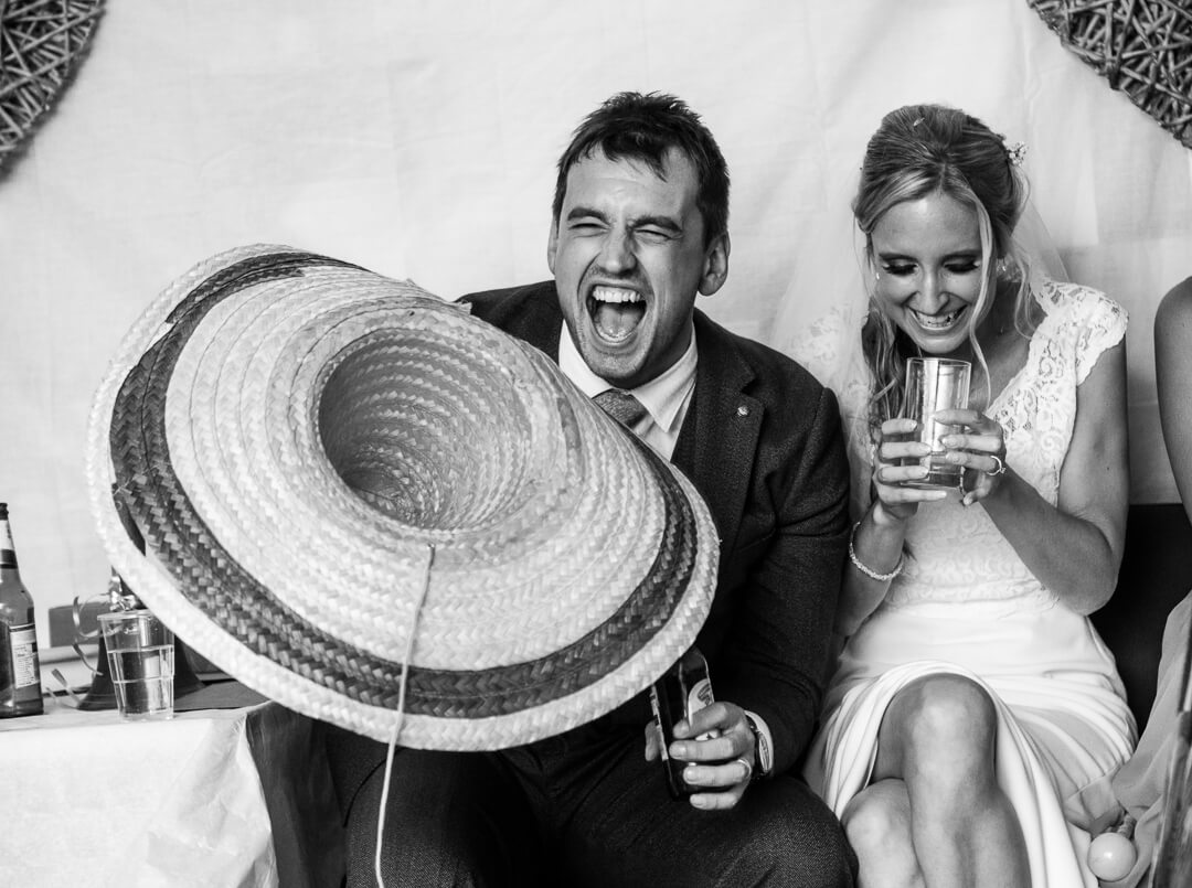 Groom holding mexican hat laughing at best mans wedding speech