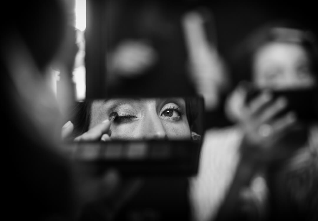 Bride looking in mirror putting on make up at wedding preparations