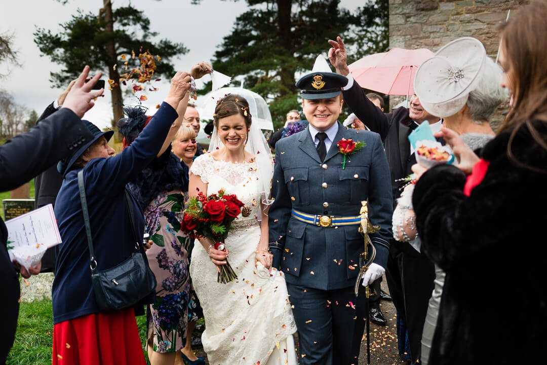 Bride with red roses and groom in RAF uniform walking through confetti