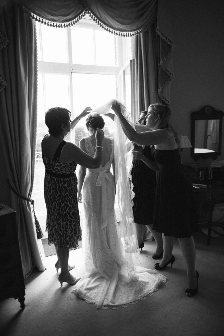 Silhouette of bride having her veil put on at wedding