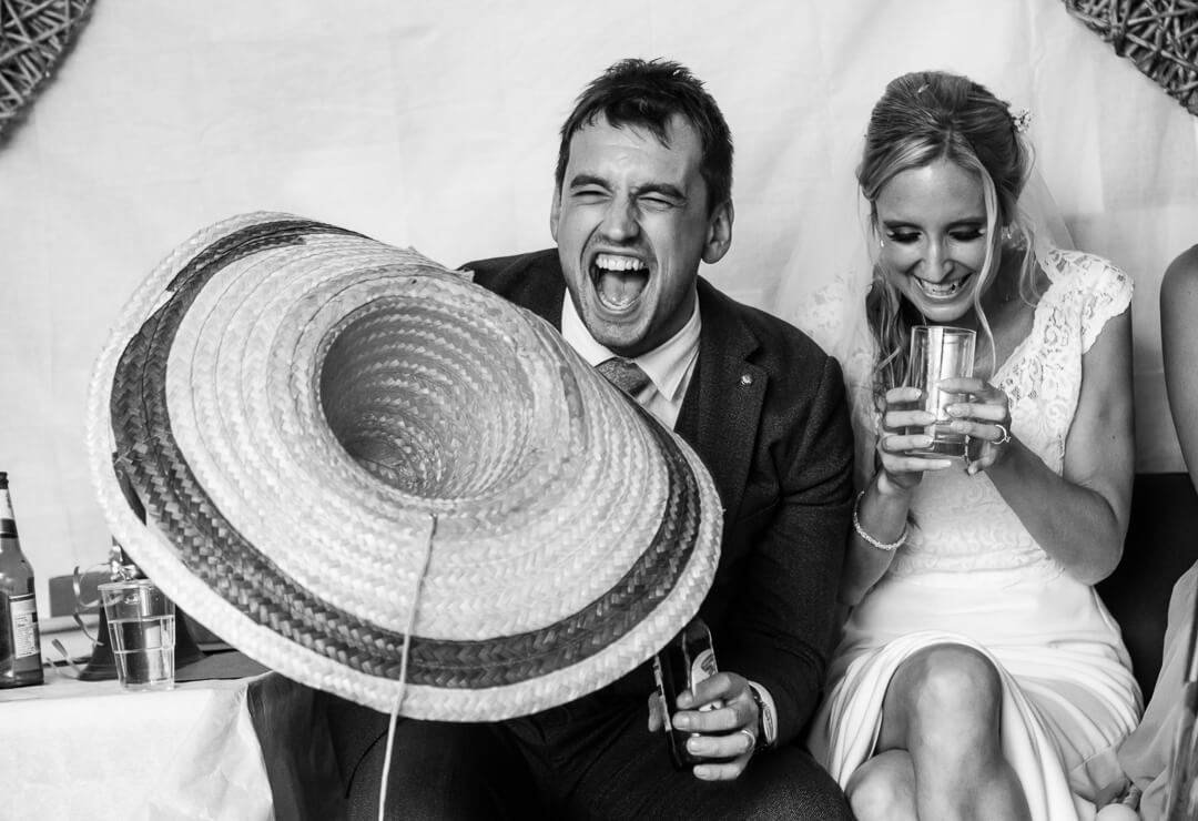 Reportage wedding photograph of groom laughing with big mexican hat at the best mans speeches