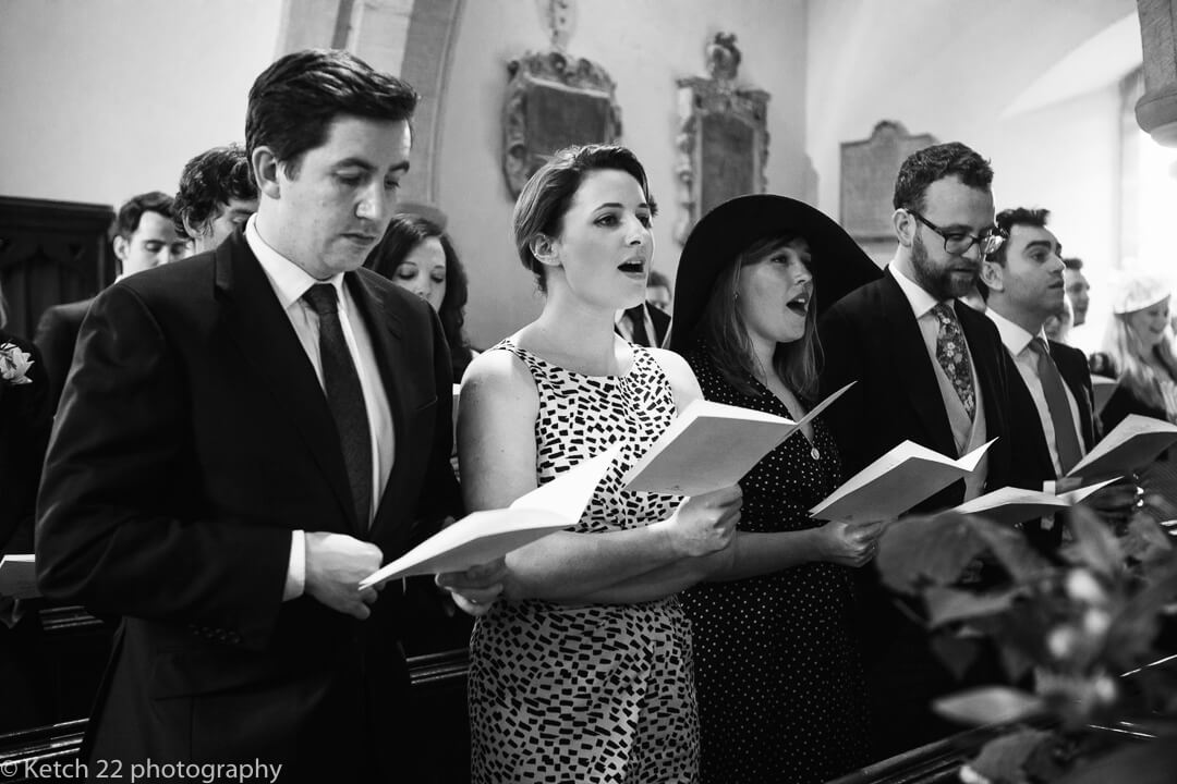 Wedding guests singing in church in Gloucestershire