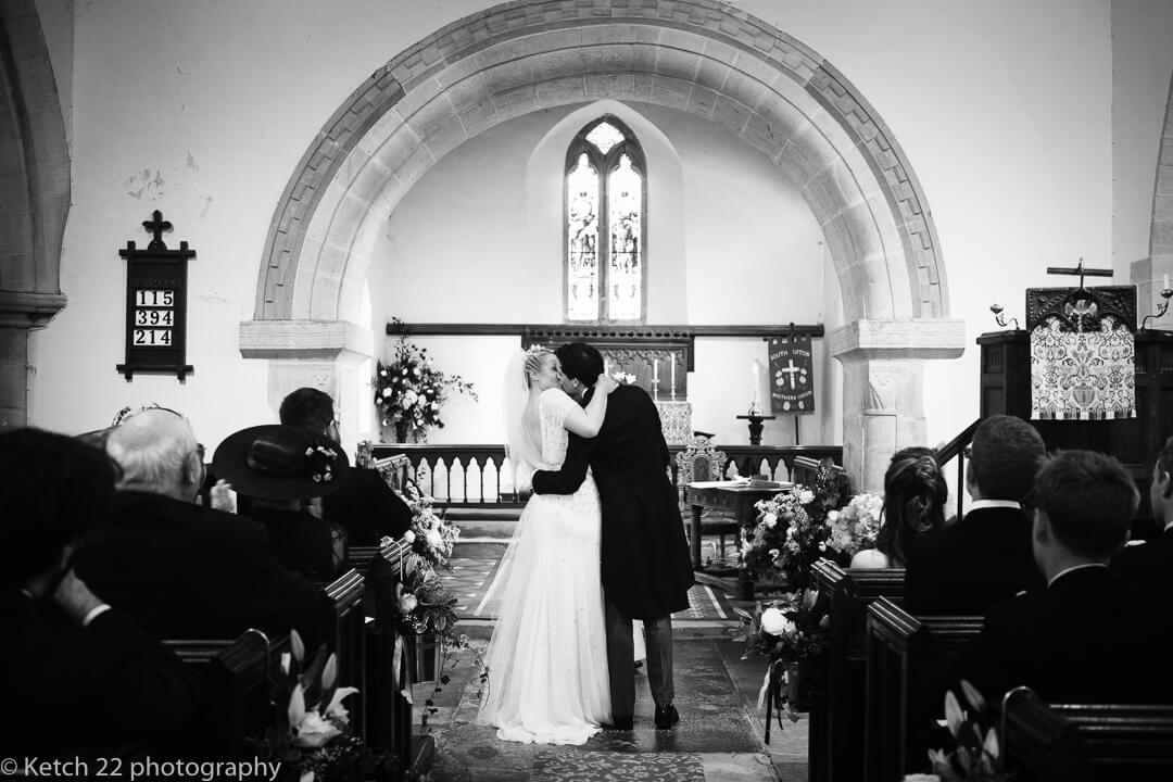 Bride and groom kissing in church at the end of the wedding ceremony