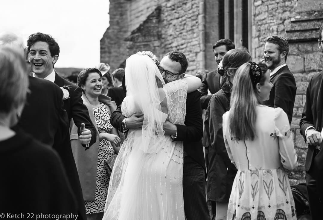Bride hugging wedding guest outside church