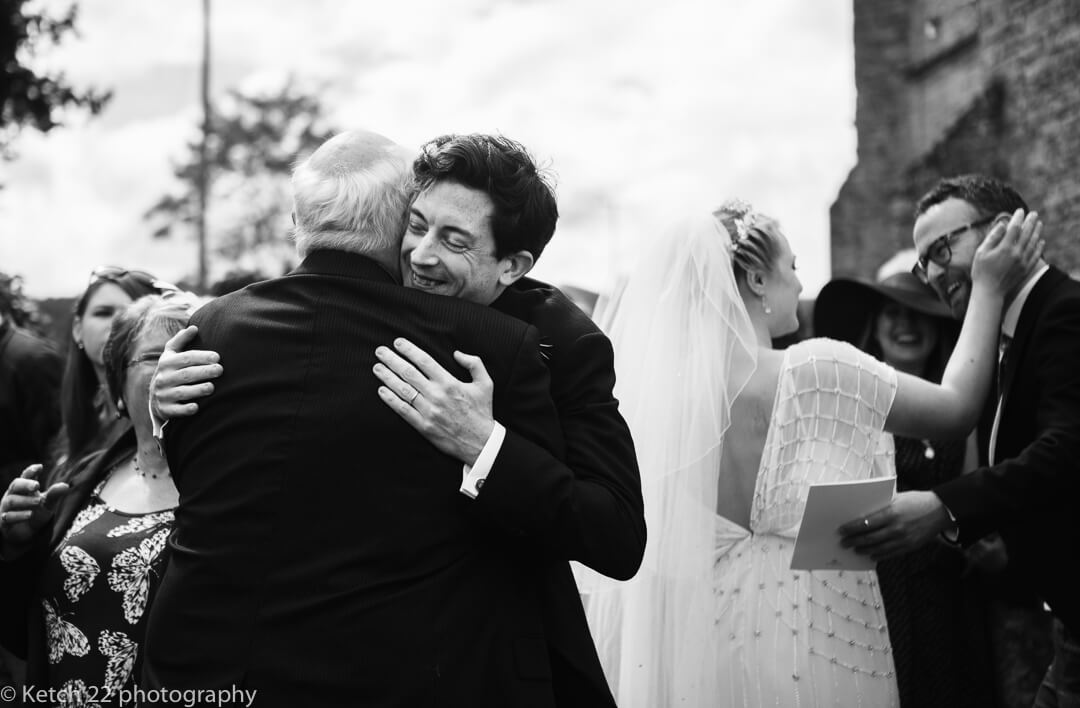 Groom hugging wedding guest after ceremony