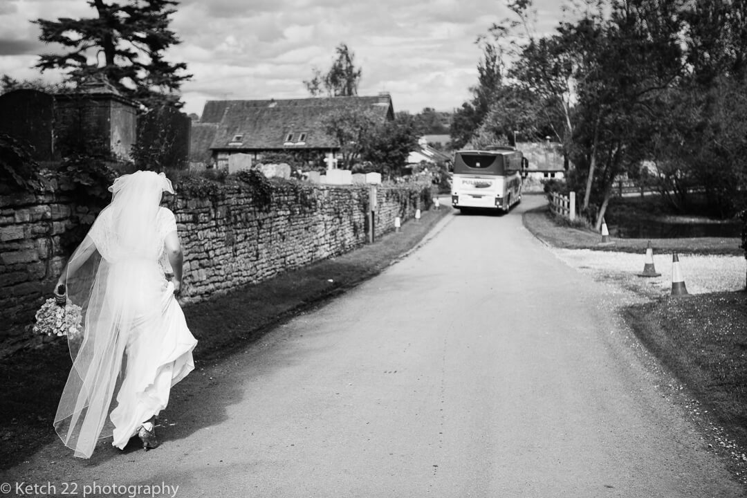 Bride walking down country lane as wedding bus leaves
