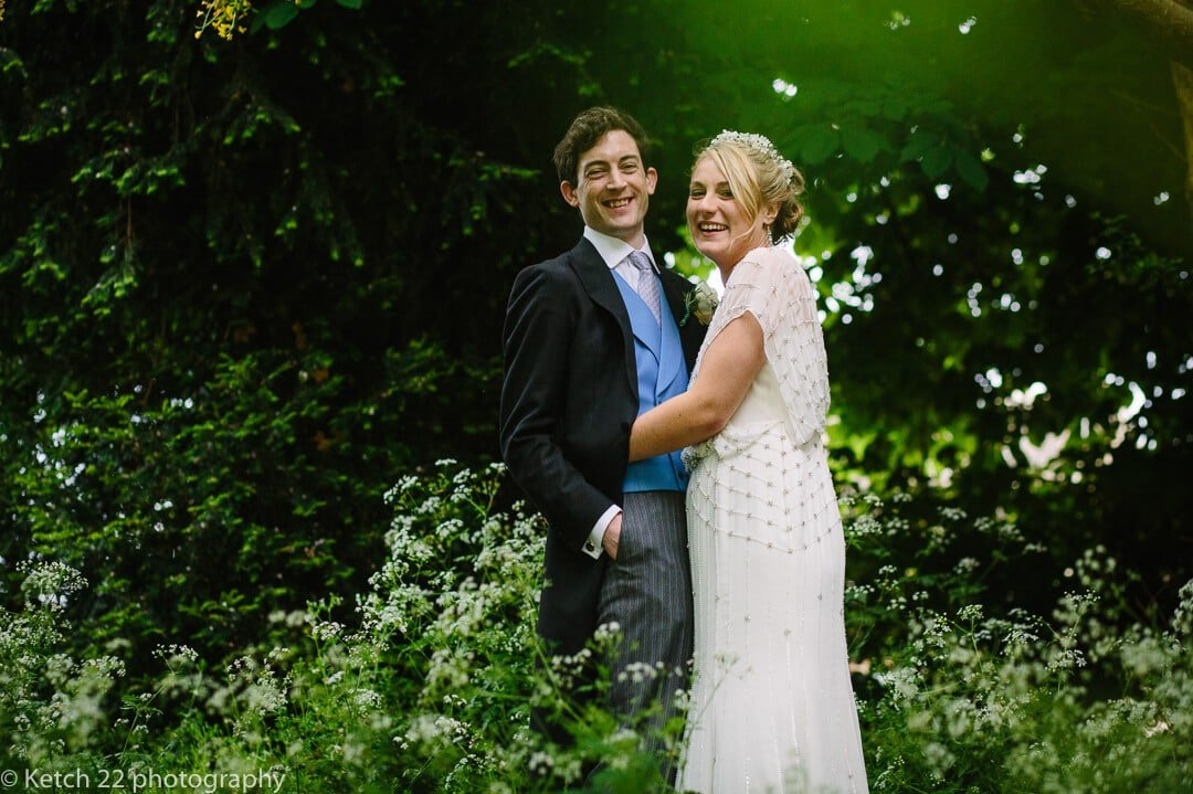 Portrait of bride and groom looking happy in garden