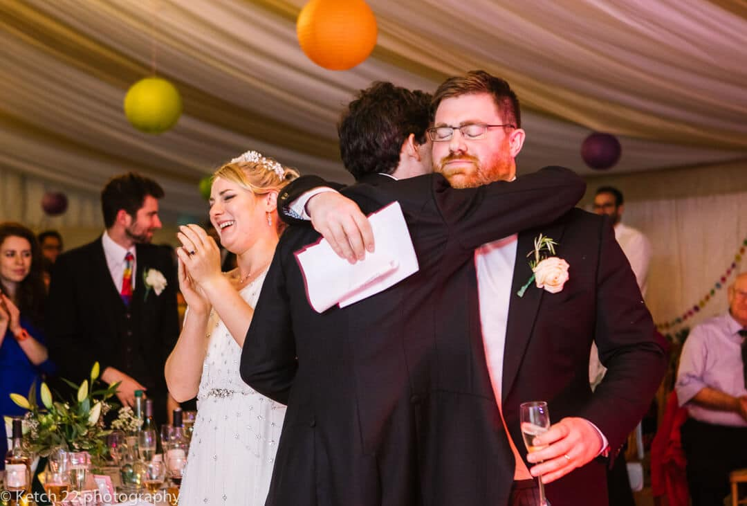 Groom hugging best man after wedding speech