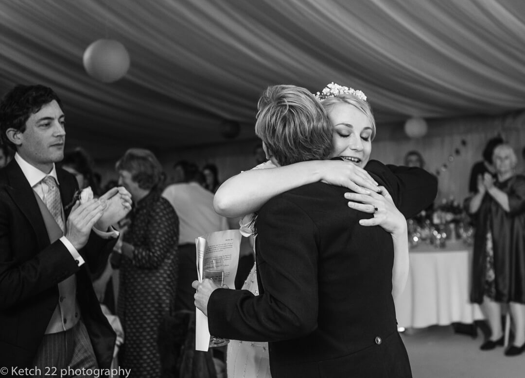 Bride hugging best man after wedding speech