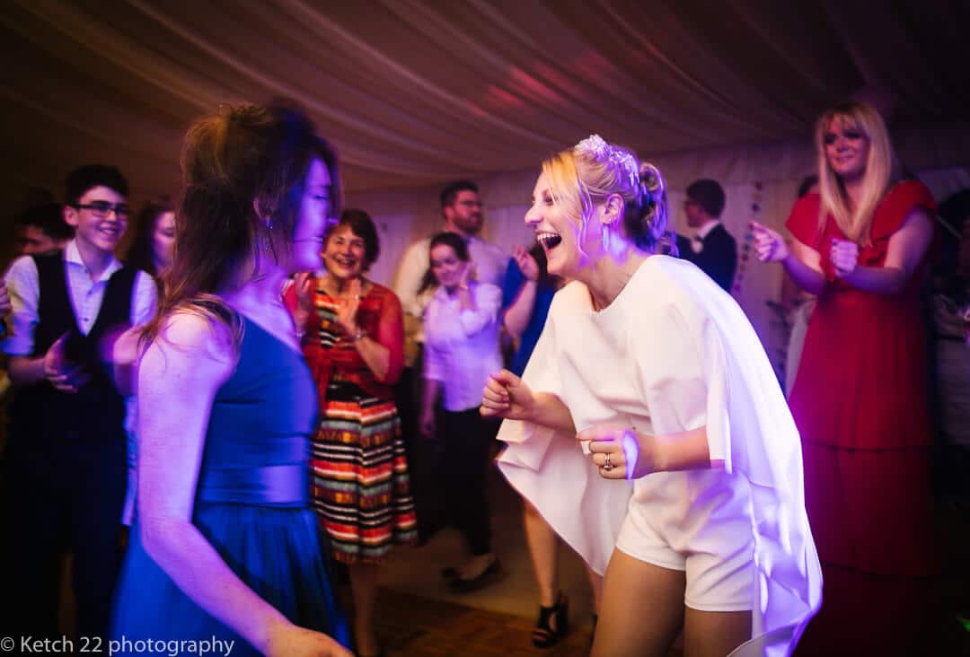 Bride in white shorts dancing at wedding reception