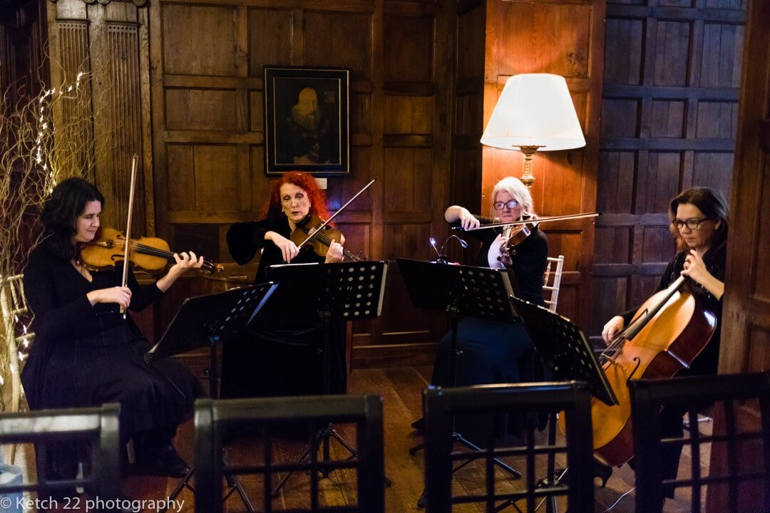 Candid wedding photo of 3 piece orchestra playing music at wedding