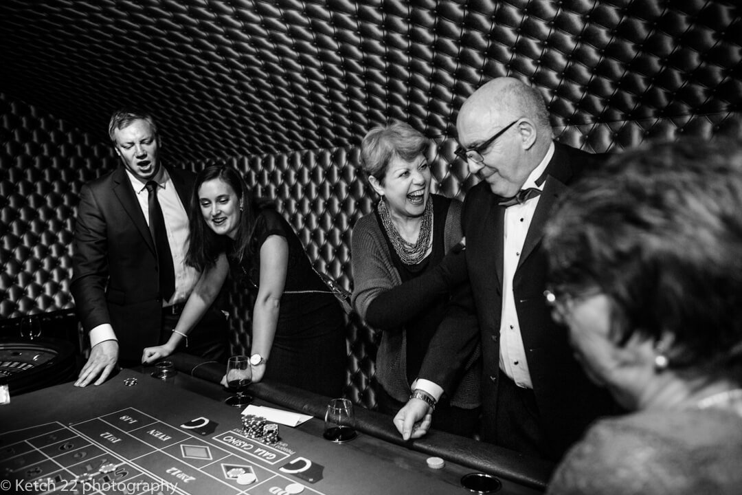 Guests laughing and enjoying casino at documentary wedding