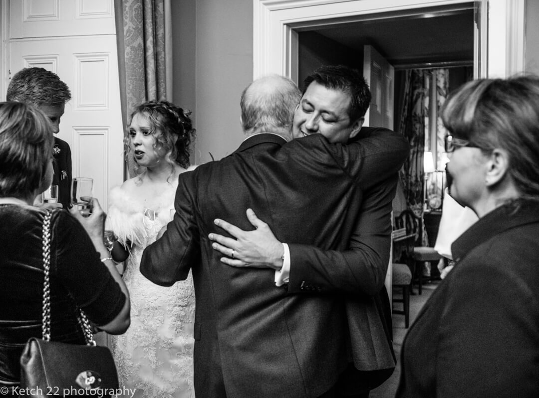 Reportage wedding photography of groom hugging guest