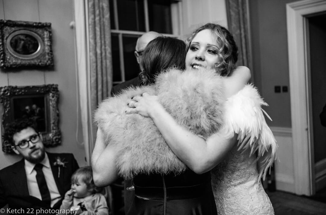 Candid wedding photo of bride hugging guest at North Cadbury Court