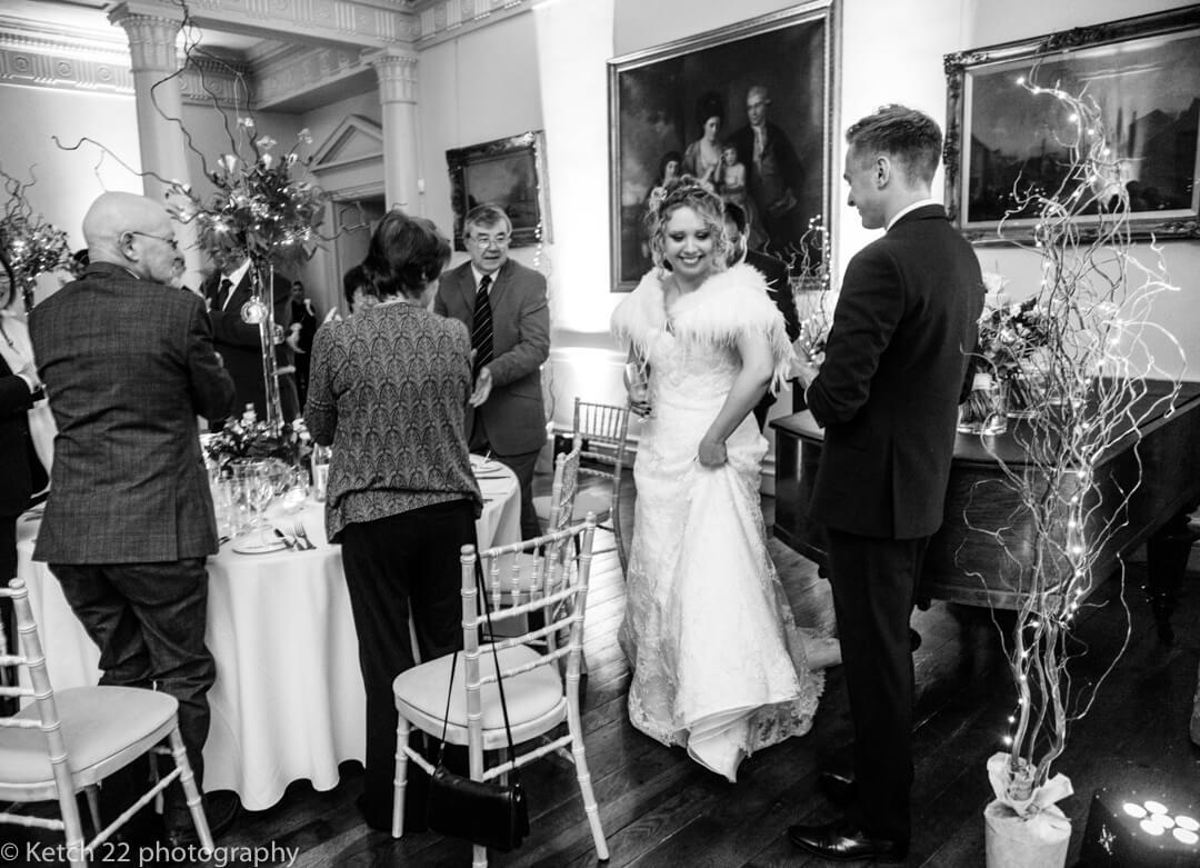 Photojournalistic wedding photo of bride entering dining room