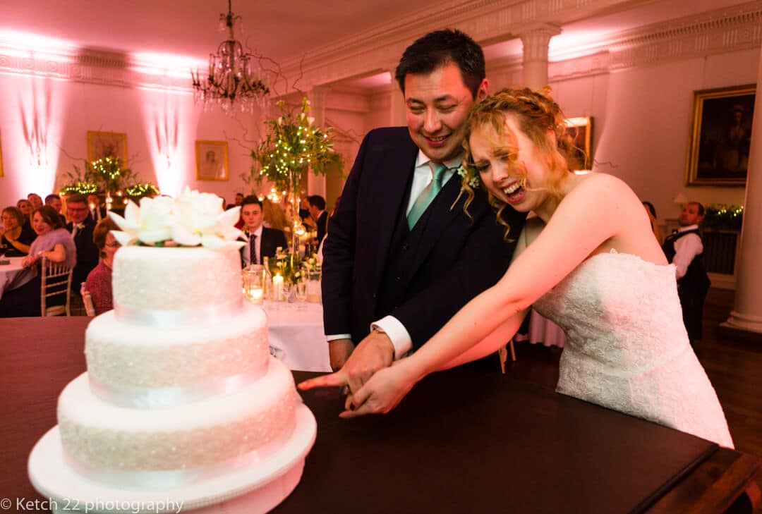 Documentary wedding photo of bride and groom cutting cake