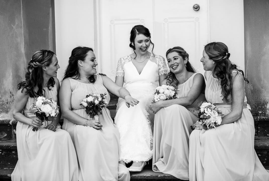 Bride and bridesmaids relaxing on steps at Homme House Wedding