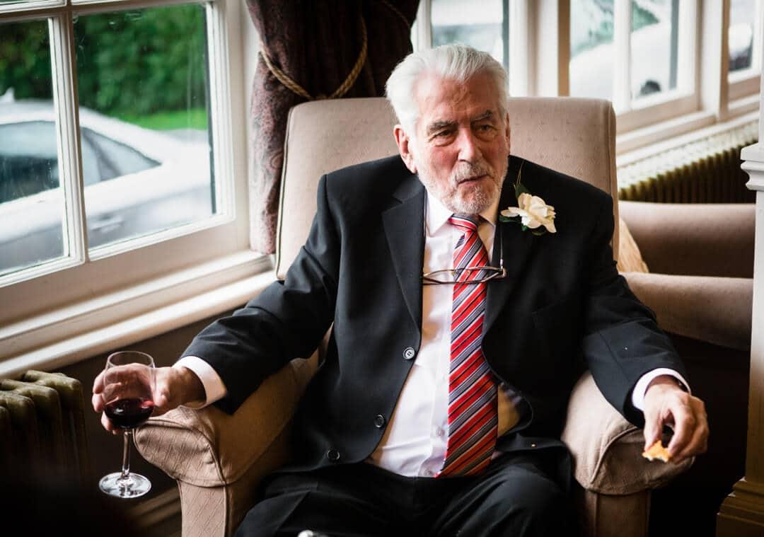 Grandad enjoying glass of wine at wedding