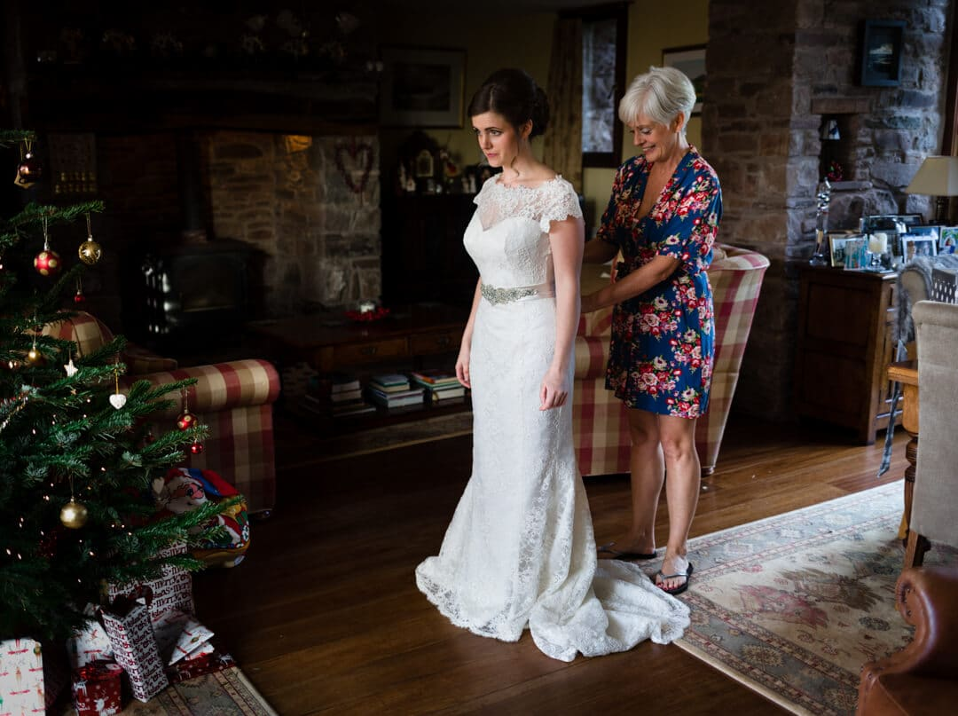 Mother helping bride with her wedding dress