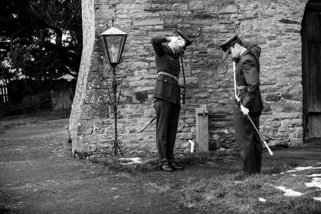 Groomsmen in RAF uniform checking their swords