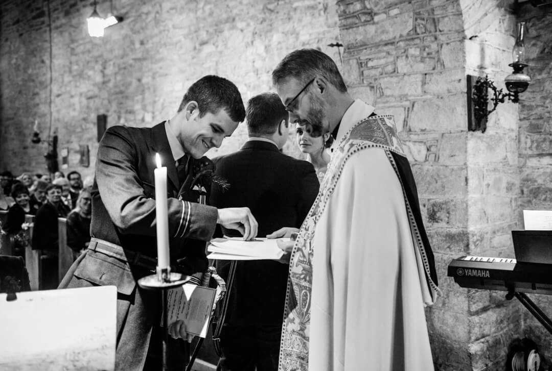 Best man handing rings to vicar at wedding