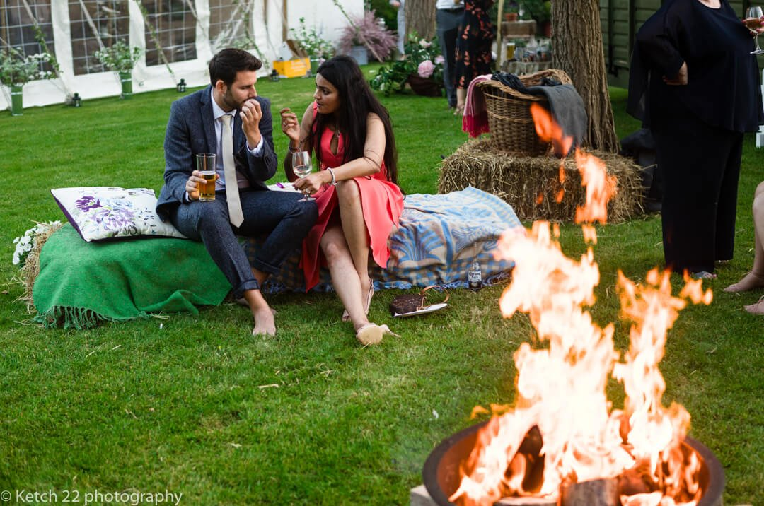 Wedding guests kick off their shoes and relax by the fire