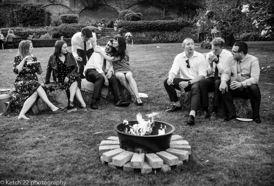 Guests sit around fire on straw bales at Marquee wedding