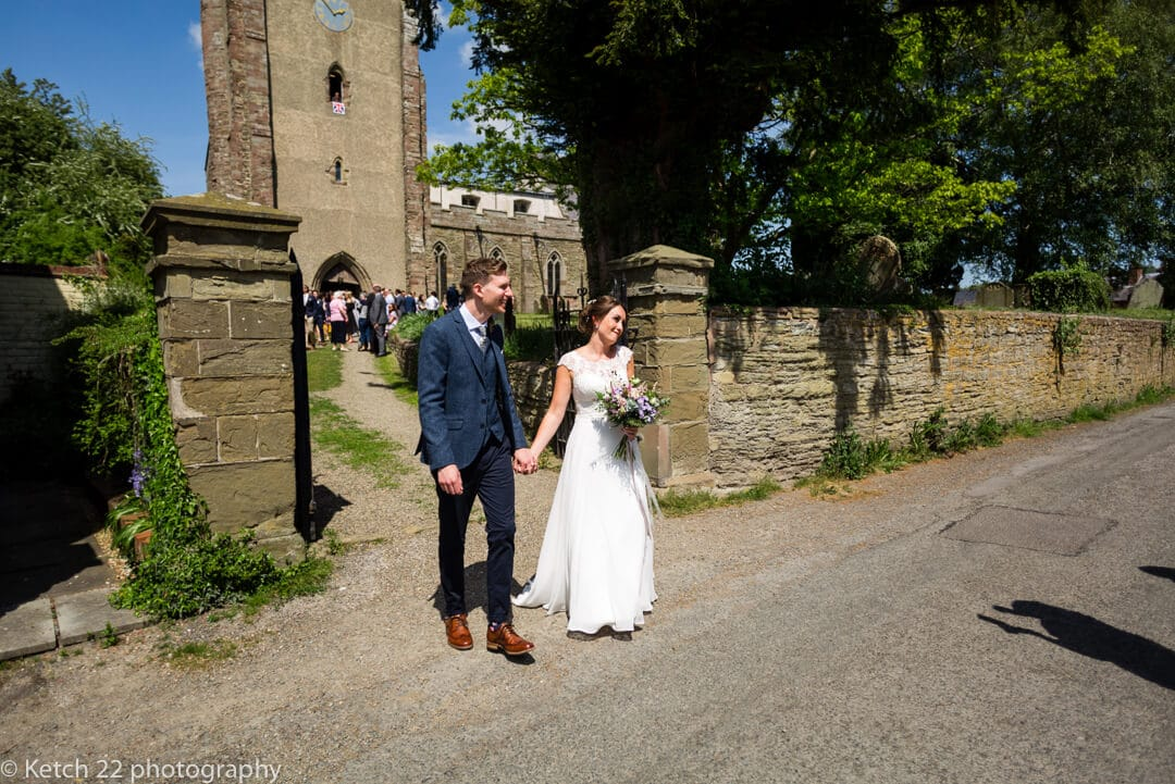 Bride and groom outside rural church after wedding