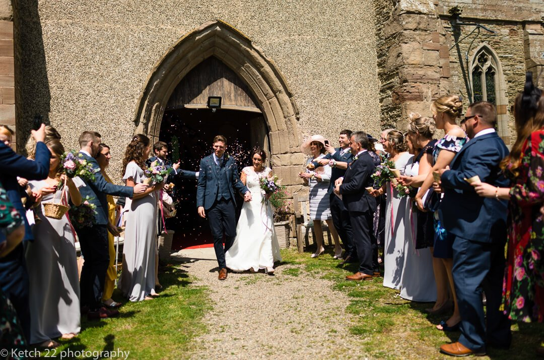 Bride and groom leaving church and getting showered with confetti