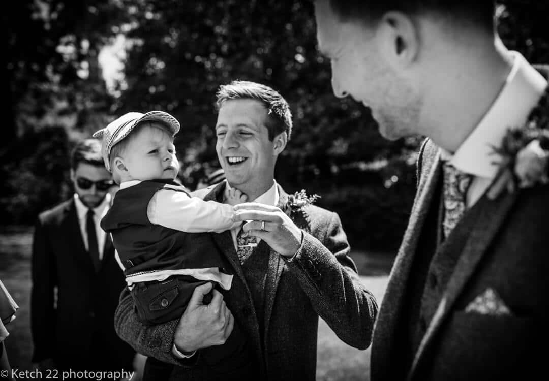 Candid photo of father and baby at rural wedding
