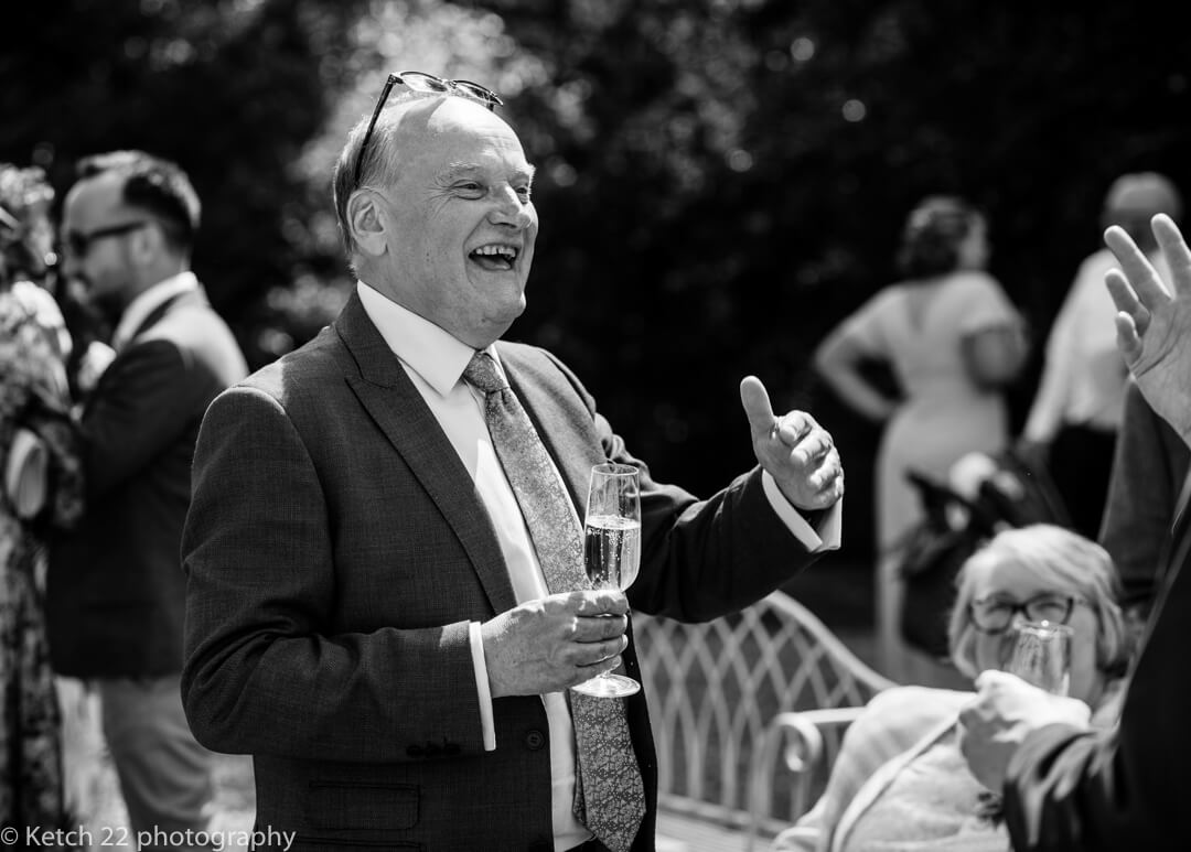 Wedding guest on lawn with champagne