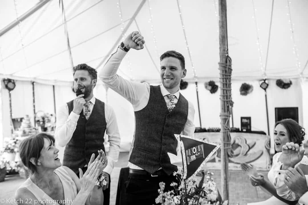 Groom fist pumping the air during wedding speech