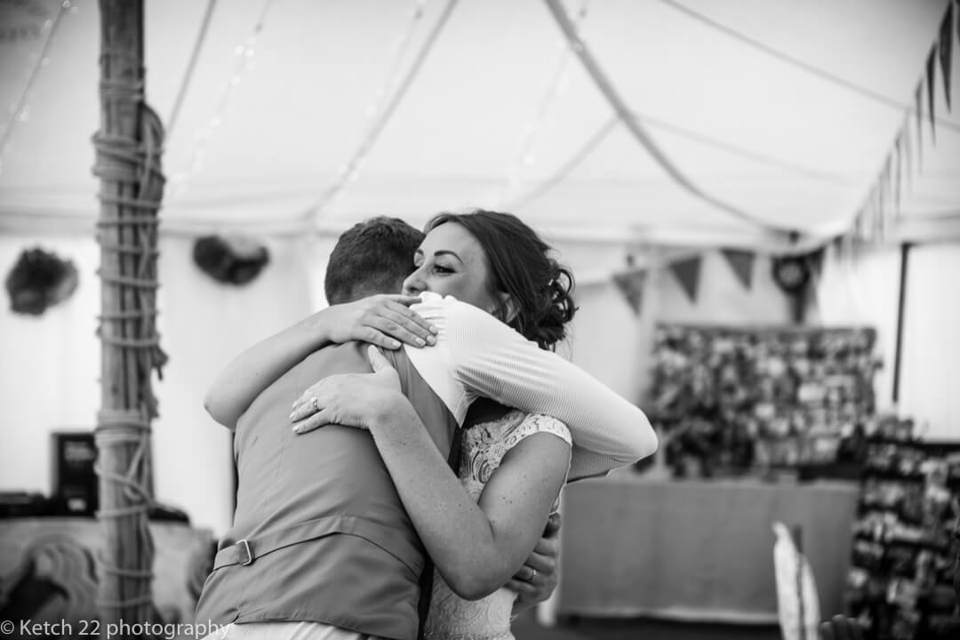 Bride and groom hugging after wedding speeches